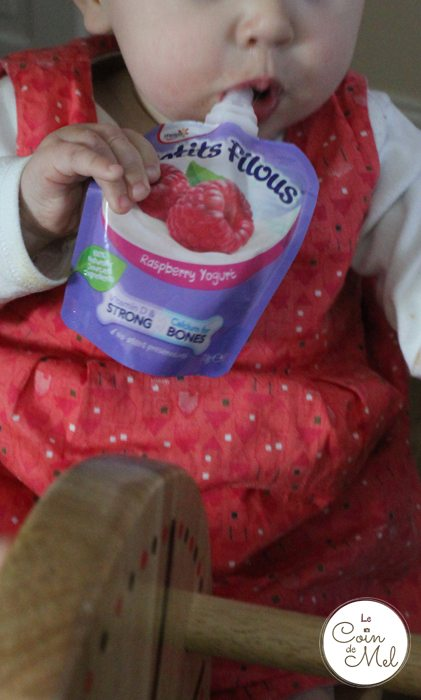 Babies can multitask - eating yghurt and riding a rocking horse