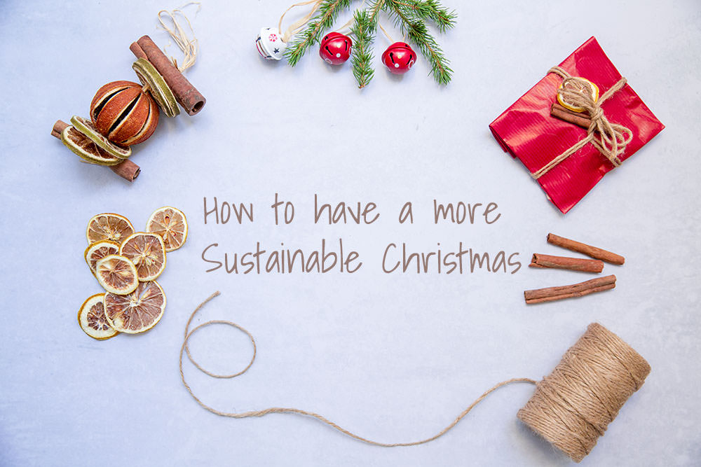 This is the featured image for this blog post, with the title in the middle, How to have a more sustainable Christmas, as well as eco-conscious wrapping options all around - cinnamon sticks, twine, metal bells, recycled paper, dried oranges