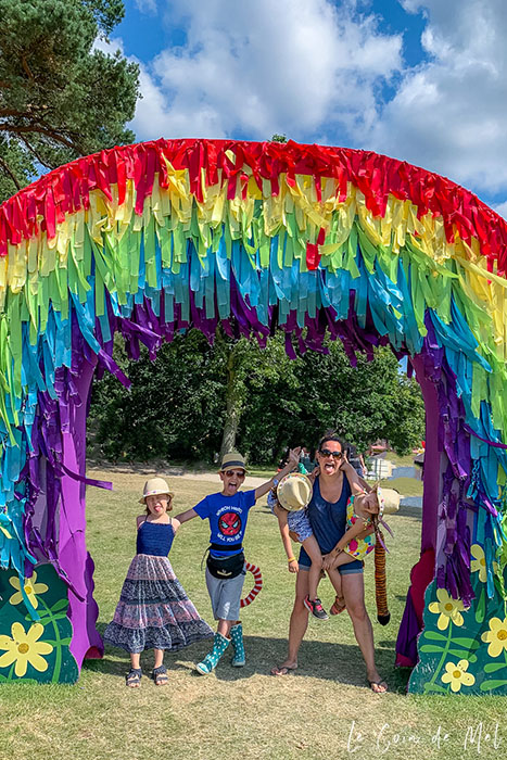 My 4 children and I at Camp Bestival in 2019. We are all pulling faces and standing under a giant rainbow arch. I am wearing my Ray-Ban RB4068 sunglasses and all my children are wearing straw hats. I am carrying my youngest two girls.