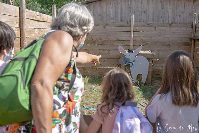 My mum and three of my children and staying near one of the activities in the maze at La Ferme Souchinet - They are working as a team to guess which of the ropes on the floor is attached to the picture of a donkey