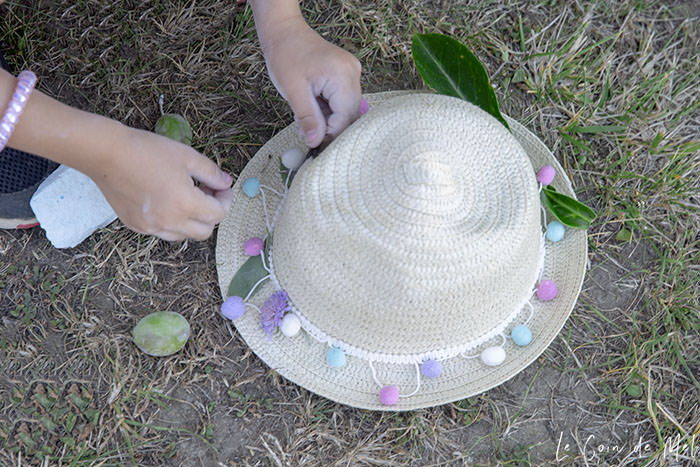 Using leaves collected in our Nature Scavenger Hunt to decorate a hat