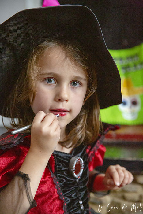 My youngest daughter, dressed as a witch, putting bright lipstick on before Halloween Treasure Hunt