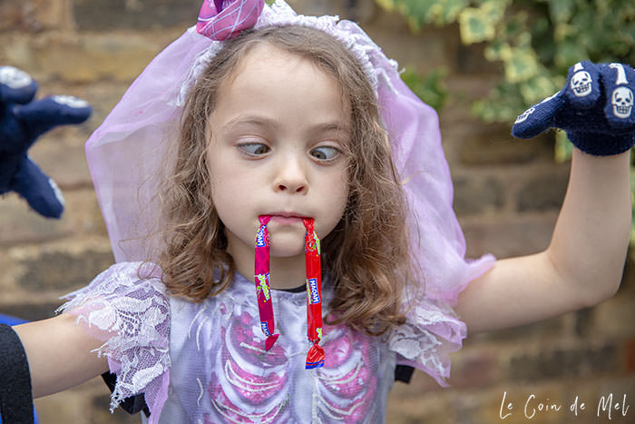 My little girl, dressed as a spooky bride, using 2 MAOAM Joystixx as fangs after our Halloween Treasure Hunt