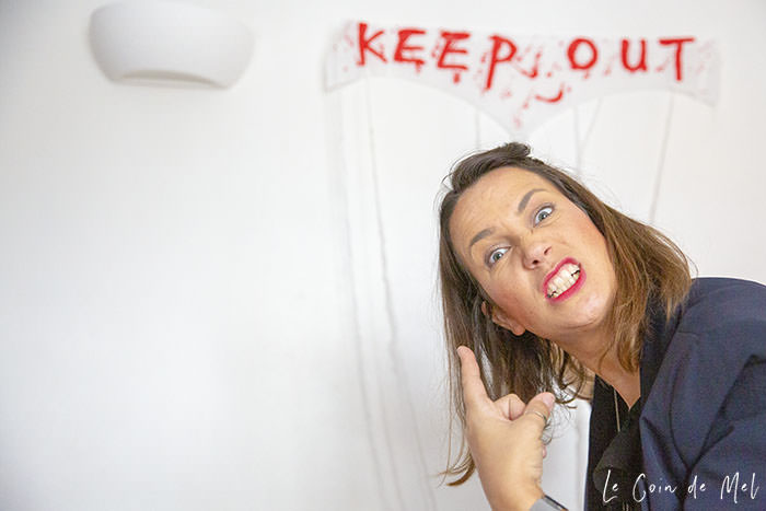 Me, looking cross, pointing at a 'Keep Out' sign on the wall, just before our Halloween Treasure Hunt