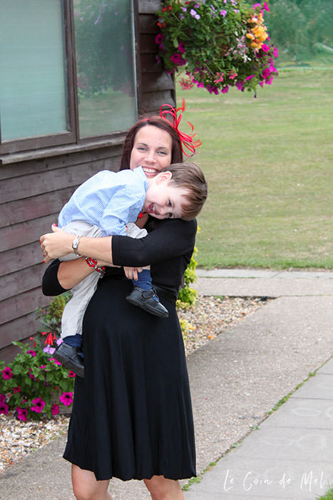 This is me, heavily pregnant with my first girl and carrying my toddler boy. I am wearing a red fascinator and a black dress. My son is laughing.