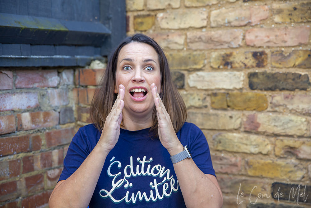 This is me about to sneeze. My eyes are wide open, my hands getting close to my mouth and nose and the sneeze is coming! I am wearing a blue T-shirt that says 'édition limitée' and in the background you can see the brick wall in my garden.