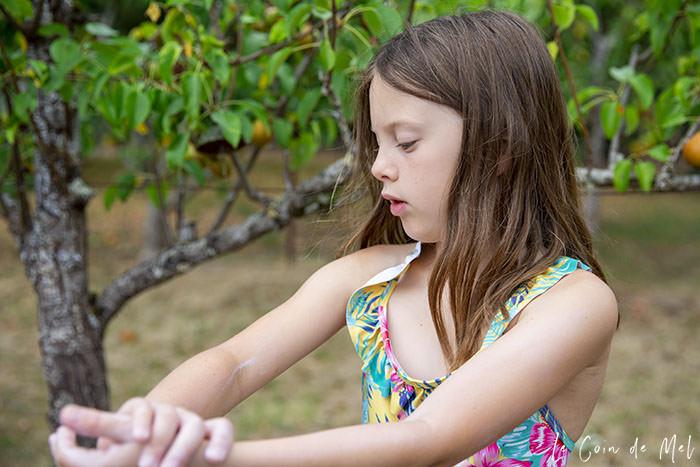 Crevette applying sun cream to her arm.