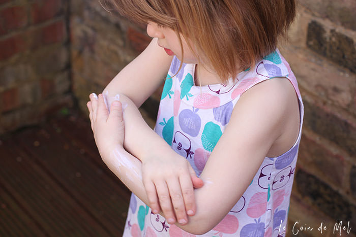 Beanie, about 3 or 4 years old. She is wearing a sleeveless top with an apple pattern and she's applying sunscreen to her arms.