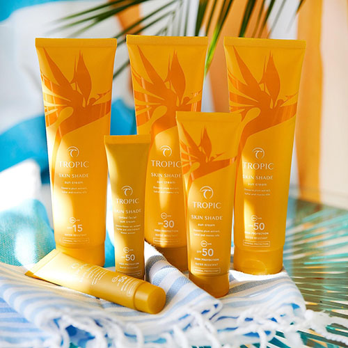 This photograph shows the entire Skin Shade collection by Tropic. The tubes are orange and there is light coming from the left.