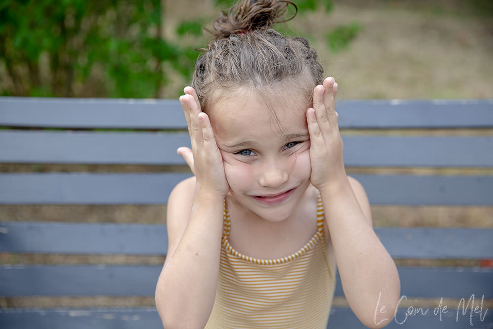 Wriggly in her yellow swimsuit, sat on a bench outside and rubbing sunscreen onto her face.