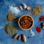 In the middle of the image, you can see our nut-free korma paste recipe all finished: the curry paste is in a bamboo bowl and all around, on a dark blue background, are the ingredients included in the recipe: garlic, coconut, garam masala, cumin seeds, fresh turmeric, peppercorns, salt, paprika, fresh ginger, chilli flakes and coriander seeds