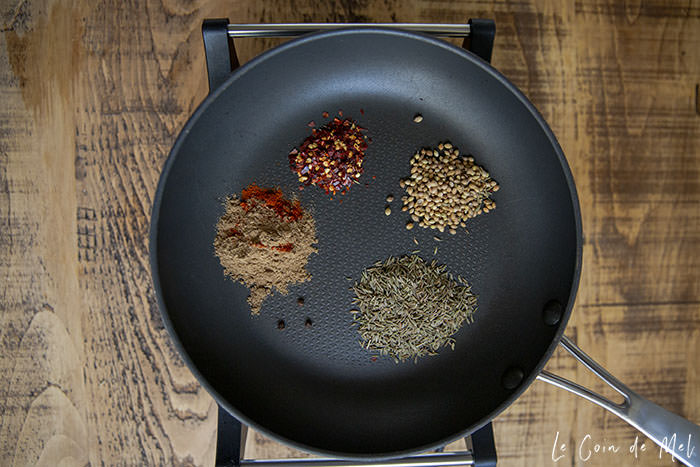 In a pan placed over a hot plate on a wooden table are all the dry spices needed to make our Nut-free Korma Paste Recipe